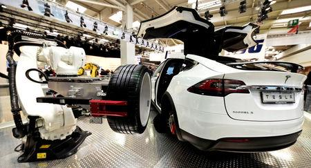"""FILE PHOTO: A robotic arm changes the tyre of a Tesla car at the world's biggest industrial fair, """"Hannover Fair\"""