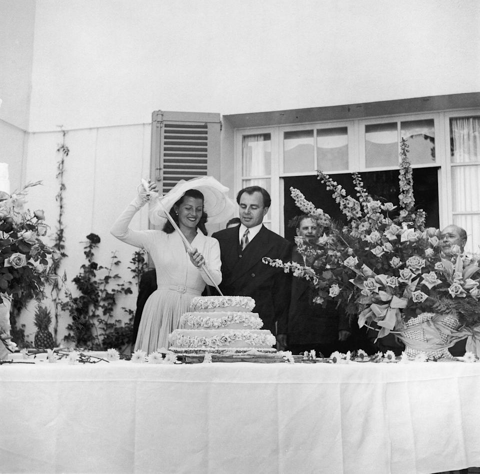 <p>Hollywood film star Rita Hayworth met Prince Aly Khan while visiting the French Rivera. The couple wed shortly after in 1949 in the South of France, naturally. Here, they cut the cake with a sword on their wedding day. They had one child together, a daughter and were married until 1953.</p>