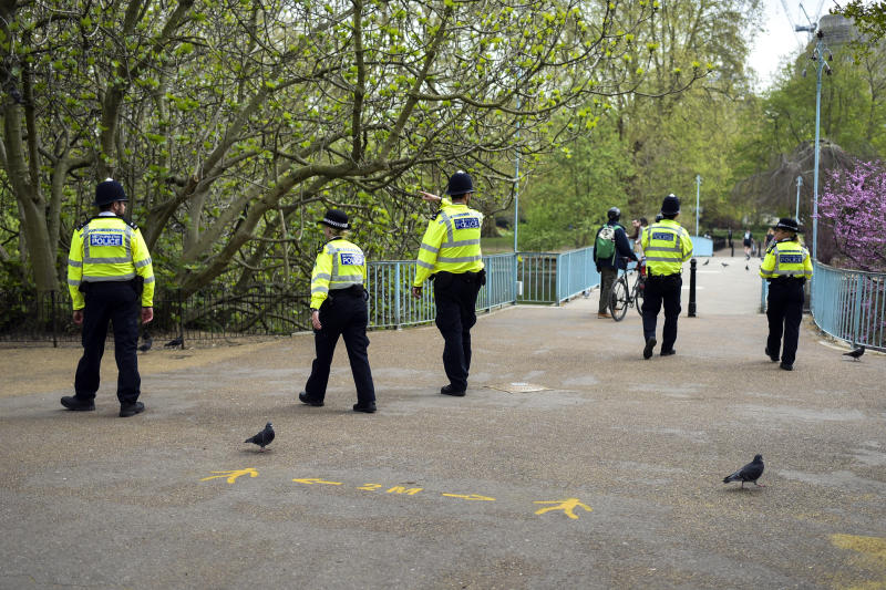 Police officers patrol St James's Park, during lockdown due to the coronavirus outbreak, in London, Thursday, April 16, 2020. The British government is promising to test thousands of nursing home residents and staff for the new coronavirus, as it faces criticism for failing to count care-home deaths in its tally of victims. (AP Photo/Alberto Pezzali)
