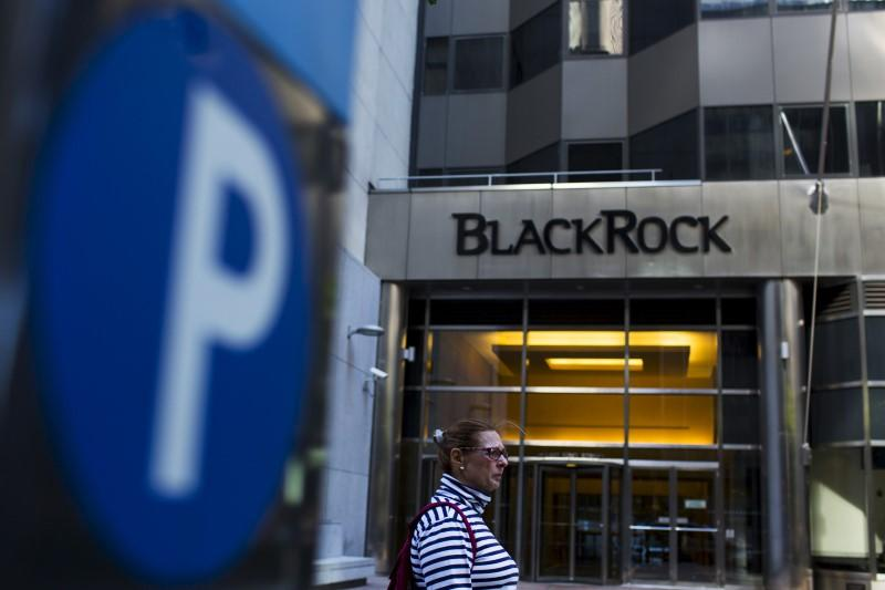 A woman walks next to a BlackRock sign pictured in the Manhattan borough of New York