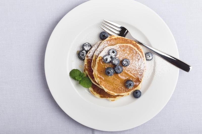 Blueberry pancakes on white plate viewed from above