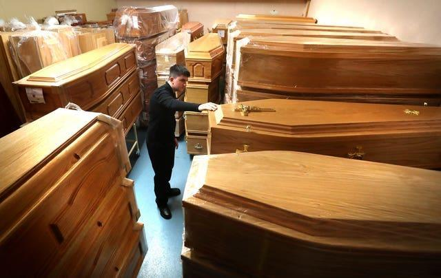 Declan Harley from Anderson Maguire Funeral Directors checks the empty coffins in the storage room at their offices in Glasgow (Andrew Milligan/PA)