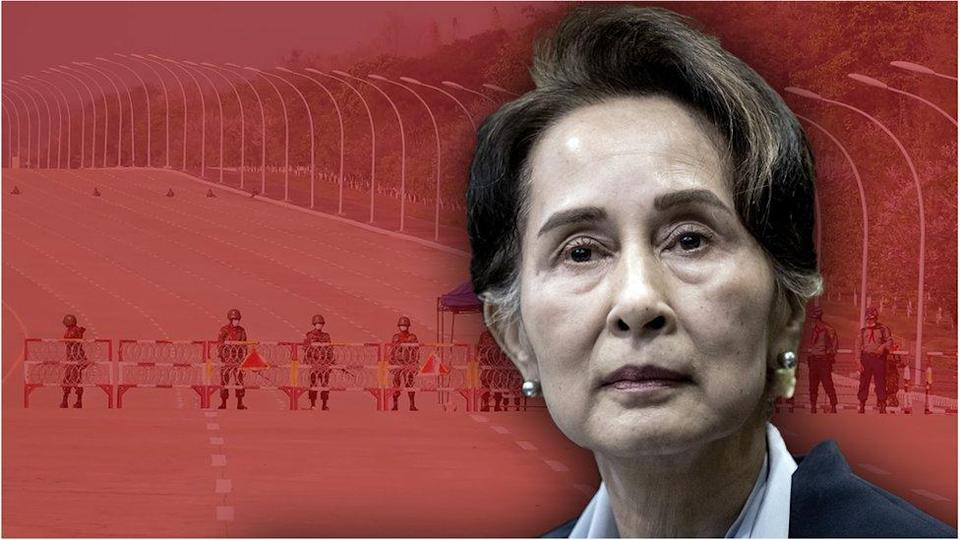 Cutout of Myanmar`s Aung San Suu Kyi against a backdrop of soldiers standing guard on a blockaded road to Myanmar`s parliament in Naypyidaw on February 1, 2021