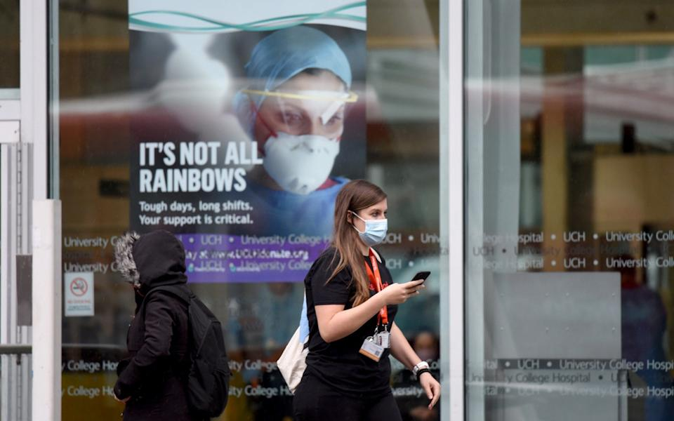 A woman walks past a sign at the University College Hospital in central London - Anadolu Agency