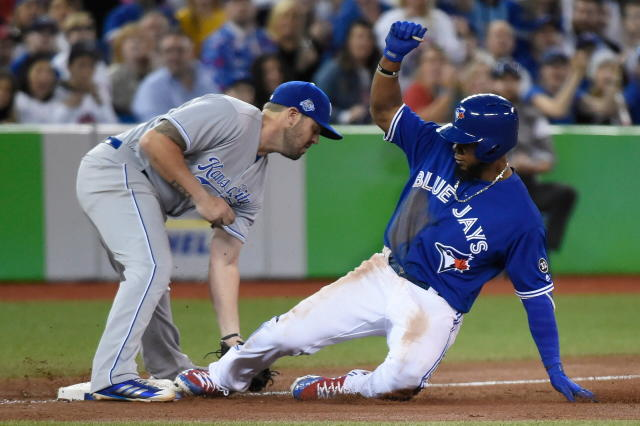 Toronto Blue Jays' Teoscar Hernandez (37) slides into third base for a two-run triple as Kansas City Royals third baseman Mike Moustakas (8) is late on the tag during the seventh inning of a baseball game Wednesday, April 18, 2018, in Toronto. (Nathan Denette/The Canadian Press via AP)