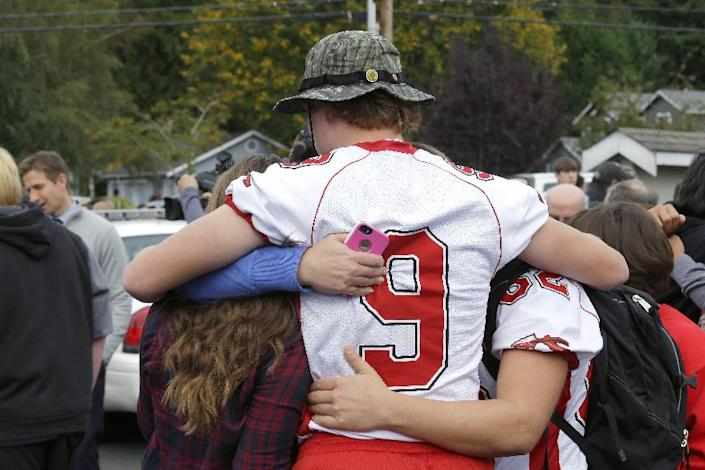 Students comfort each other following a shooting at Marysville-Pilchuck High School in Washington. (AP/Ted S. Warren)  CLICK for slideshow on Washington State school shooting.