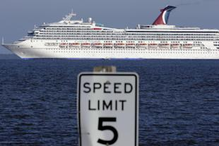 The cruise ship Carnival Triumph enters Mobile Bay near Dauphin island, Ala., Thursday, Feb. 14, 2013. The ship with more than 4,200 passengers and crew members has been idled for nearly a week in the Gulf of Mexico following an engine room fire. (AP Photo/Dave Martin)