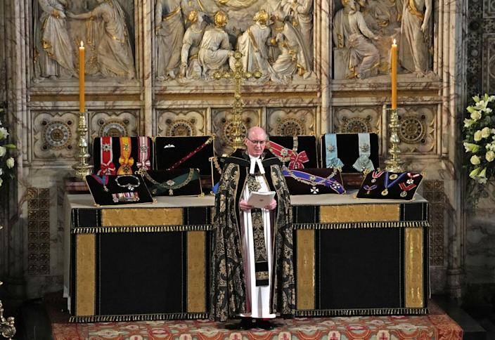 David Conner, Dean of Windsor, stands in front of an altar covered with Prince Philip's insignias.