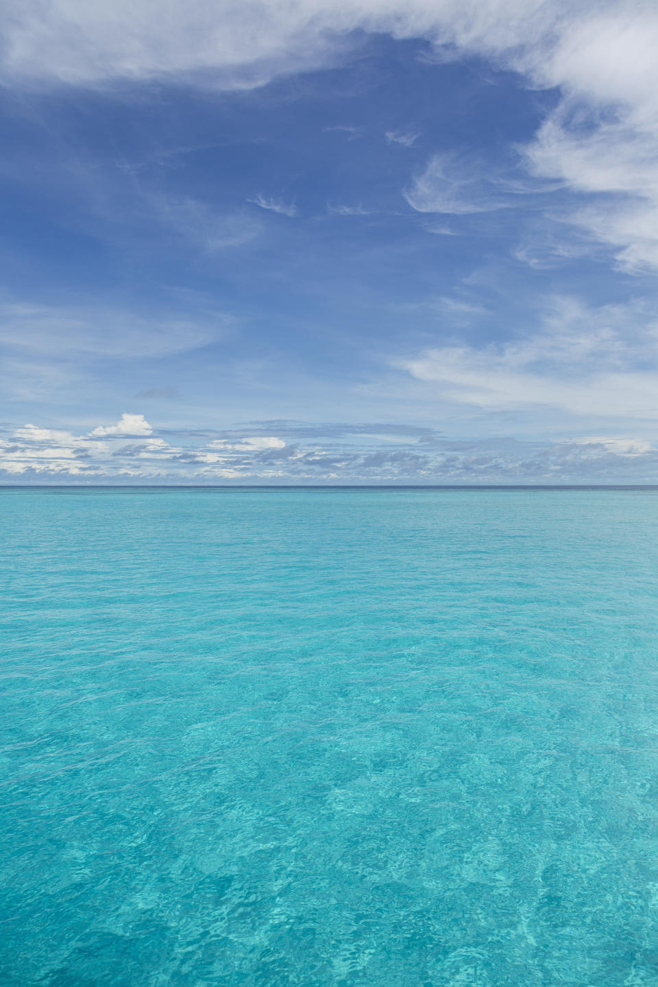 View of clear tropical water of Indian ocean with blue sky and clouds off coast of Baa Atoll, Maldives