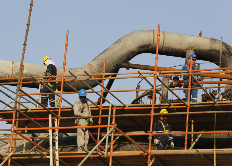 During a trip organized by Saudi information ministry, workers fix the damage in Aramco's oil separator at processing facility after the recent Sept. 14 attack in Abqaiq, near Dammam in the Kingdom's Eastern Province, Friday, Sept. 20, 2019. Saudi Arabia allowed journalists access Friday to the site of a missile-and-drone attack on a facility at the heart of the kingdom's oil industry, an assault that disrupted global energy supplies and further raised tensions between the U.S. and Iran. (AP Photo/Amr Nabil)