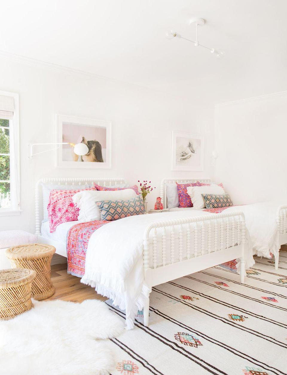 <p>If your teens share one large room, consider two queen beds instead of two twin-sized beds if you have the space. The upgrade will make sharing a room feel a lot more mature and comfortable. Incorporate boho elements with a patterned rug, bright sheets and pillows, and rattan ottomans. Abstract photography is a chic, modern touch.</p>