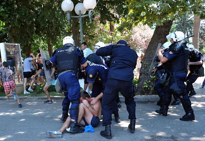 """Montenegro police officers arrest a man during the first ever pride event in the Montenegrin seaside resort of Budva, Wednesday, July 24, 2013. Dozens of extremists shouting """"Kill the gays"""" have attacked gay activists as they were gathering for the first ever pride event in staunchly conservative Montenegro. The assailants threw rocks, bottles and various other objects at some 20 gay activists and supporters and at special police securing the event in the coastal town of Budva on Wednesday. Police intervened to push the attackers away and the event continued as planned. (AP Photo/Risto Bozovic)"""