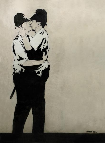 """This undated photo provided by Keszler Gallery in New York, Tuesday, Feb. 18, 2014, shows """"Kissing Coppers,"""" a black-and-white stencil of two uniformed English """"bobbies"""" (police officers) in a passionate clinch. The image was spray-painted in 2005 on the Prince Albert Pub in Brighton, England. Three works by the elusive British street artist Banksy, including two that had to be removed from the sides of buildings, are expected to bring hundreds of thousands of dollars Tuesday night at the Fine Art Auctions Miami. (AP Photo/ Keszler Gallery)"""