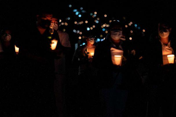 PHOTO: Health workers hold candles during a vigil to honor Manuel de Jesus Merino, a 41-year-old nurse who died of COVID-19 at IMSS Hospital Regional #1 in Tijuana in Mexico's Baja California on June 2, 2020. (Guillermo Arias/AFP via Getty Images)