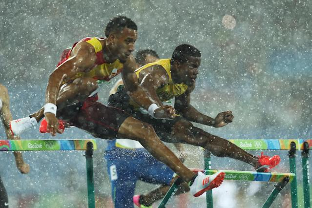 <p>Orlando Ortega of Spain and Deuce Carter of Jamaica compete in the rain during the Men's 110m Hurdles Round 1 – Heat 2 on Day 10 of the Rio 2016 Olympic Games at the Olympic Stadium on August 15, 2016 in Rio de Janeiro, Brazil. (Getty) </p>