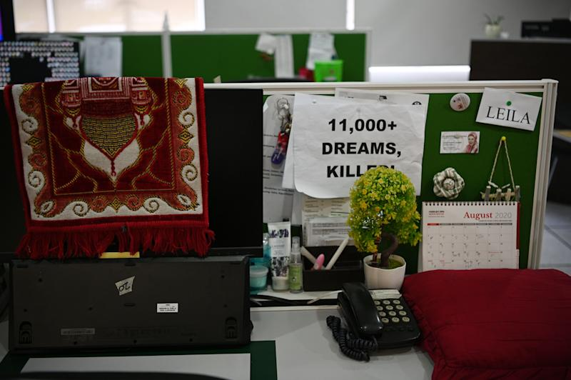 """FILE PHOTO: A placard that reads """"11,000+ dreams, killed"""" is seen pinned at a work cubicle in the ABS-CBN newsroom on the final day of work for most of its staff, at the broadcasting network's headquarters in Manila on August 31, 2020. (Photo: TED ALJIBE/AFP via Getty Images)"""