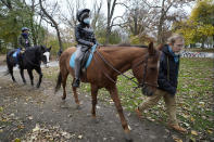 Kensington Stables trail guide Bill Zimmerman leads horseback riders along a bridle path through Prospect Park, Sunday, Nov. 15, 2020, in the Brooklyn borough of New York. The young women were given the equestrian experience as a birthday present from a family member. (AP Photo/Kathy Willens)