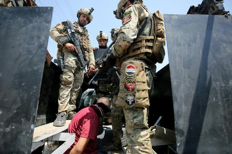 Iraq's rapid response forces detain a man as they storm a house north of Baghdad searching for wanted Islamic State group suspects on July 21, 2019