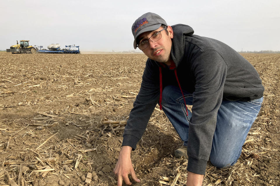 """Farmer Lance Unger describes the process of strip tillage, which disturbs the soil less than conventional tillage, in Carlisle, Indiana on April 6, 2021. Unger is among many farmers using minimum tillage, cover cropping and other methods to improve yields while storing more carbon in the soil. """"I want to make our farm better for the fourth generation,"""" he says. (AP Photo/John Flesher)"""