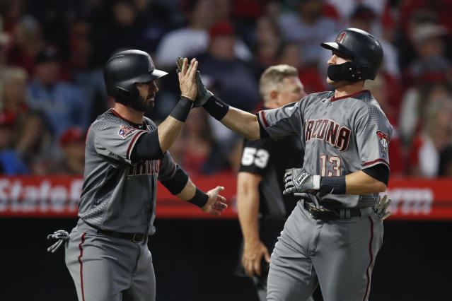 Arizona Diamondbacks' Nick Ahmed, right, and Daniel Descalso celebrate after they scored on a double hit by Jeff Mathis during the fourth inning of a baseball game against the Los Angeles Angels, Monday, June 18, 2018, in Anaheim, Calif. (AP Photo/Jae C. Hong)
