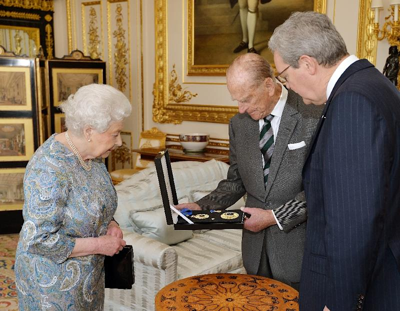 Britain's Queen Elizabeth II (L) presents Prince Philip, Duke of Edinburgh (C) with the Insignia of a Knight of the Order of Australia at Windsor Castle, on April 22, 2015