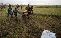 Survivors of Super Typhoon Haiyan run to get their hands onto a sack of rice dropped by a Philippine Air Force helicopter into a remote location some 25km (17 miles) west of Tacloban November 17, 2013. REUTERS/Wolfgang Rattay (