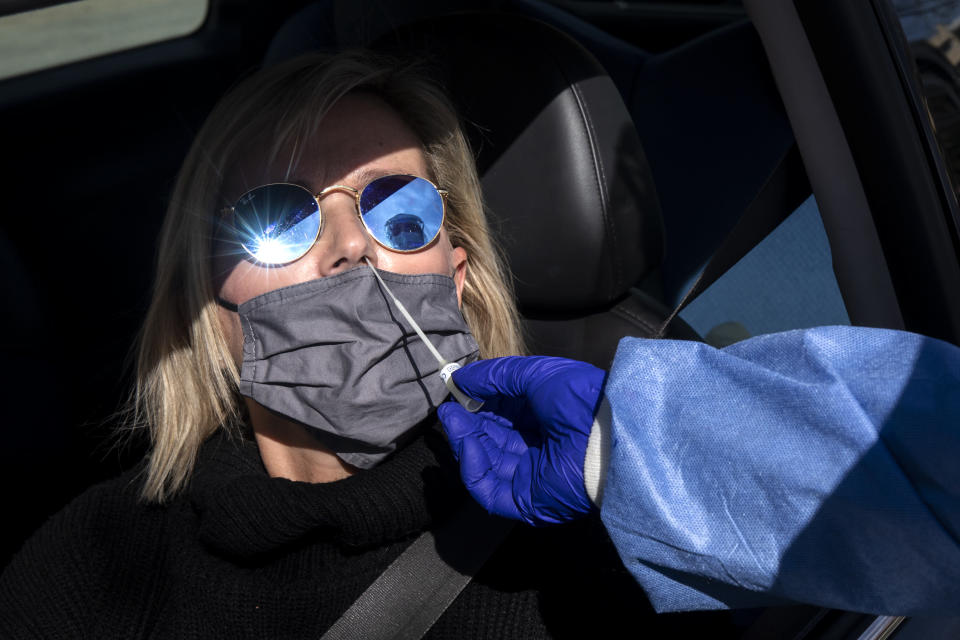 A teacher gets tested for COVID-19 at a drive-through testing site for teachers and staff of high schools, in Glyfada suburb, south of Athens, Sunday, Jan. 31, 2021. Greek authorities on Friday said they will reimpose tougher lockdown restrictions in greater Athens after a January decline in infection rates was reversed this week, but they will reopen the first three grades of high schools. (AP Photo/Yorgos Karahalis)