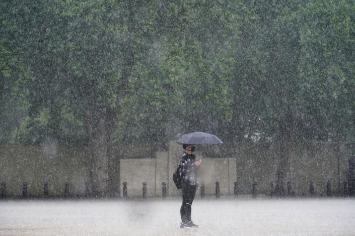 A woman stands in the rain in Horse Guards Parade in central London, Sunday July 25, 2021. Thunderstorms bringing lightning and torrential rain to the south are set to continue until Monday it is forecast. (Victoria Jones/PA via AP)