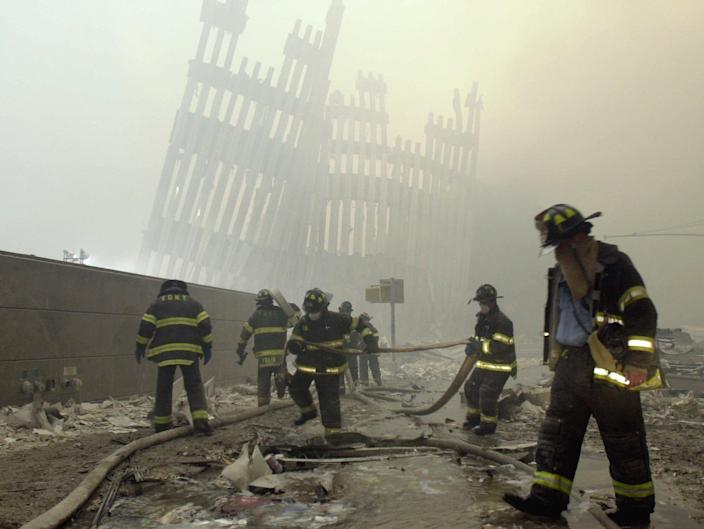 <p>With the skeleton of the World Trade Center twin towers in the background, New York City firefighters work amid debris on Cortlandt St. after the terrorist attacks on Sept. 11, 2001. (Photo: Mark Lennihan/AP) </p>