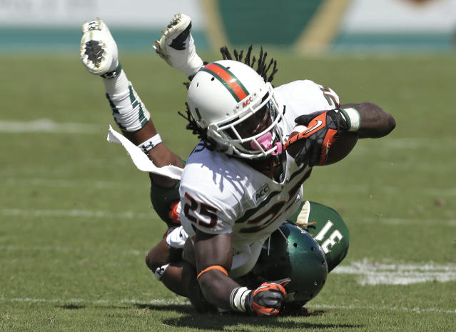 Miami running back Dallas Crawford (25) runs over South Florida defensive back Brandon Salinas (31) during the first quarter of an NCAA college football game Saturday, Sept. 28, 2013, in Tampa, Fla. (AP Photo/Chris O'Meara)