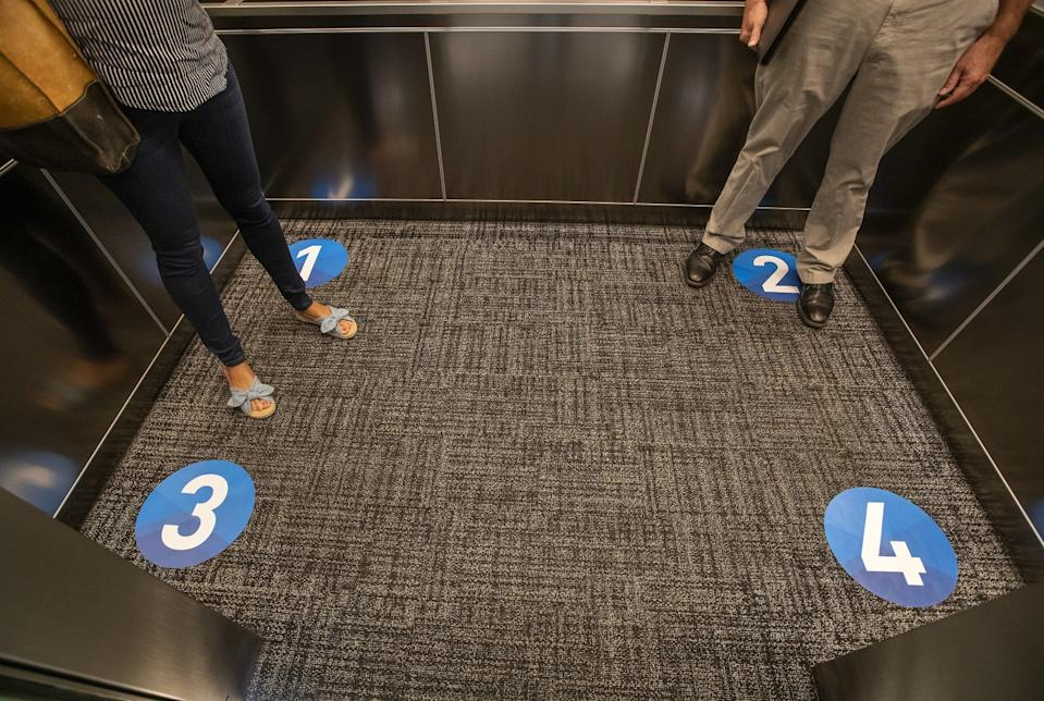 Decals labeled 1, 2, 3 and 4 on the carpeted floor of an elevator with two people inside