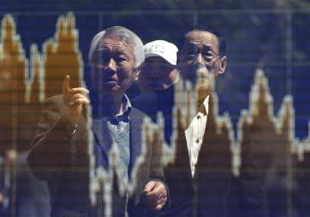 Men are reflected in a screen displaying a graph showing the movements of recent share averages outside a brokerage in Tokyo April 11, 2014. REUTERS/Issei Kato
