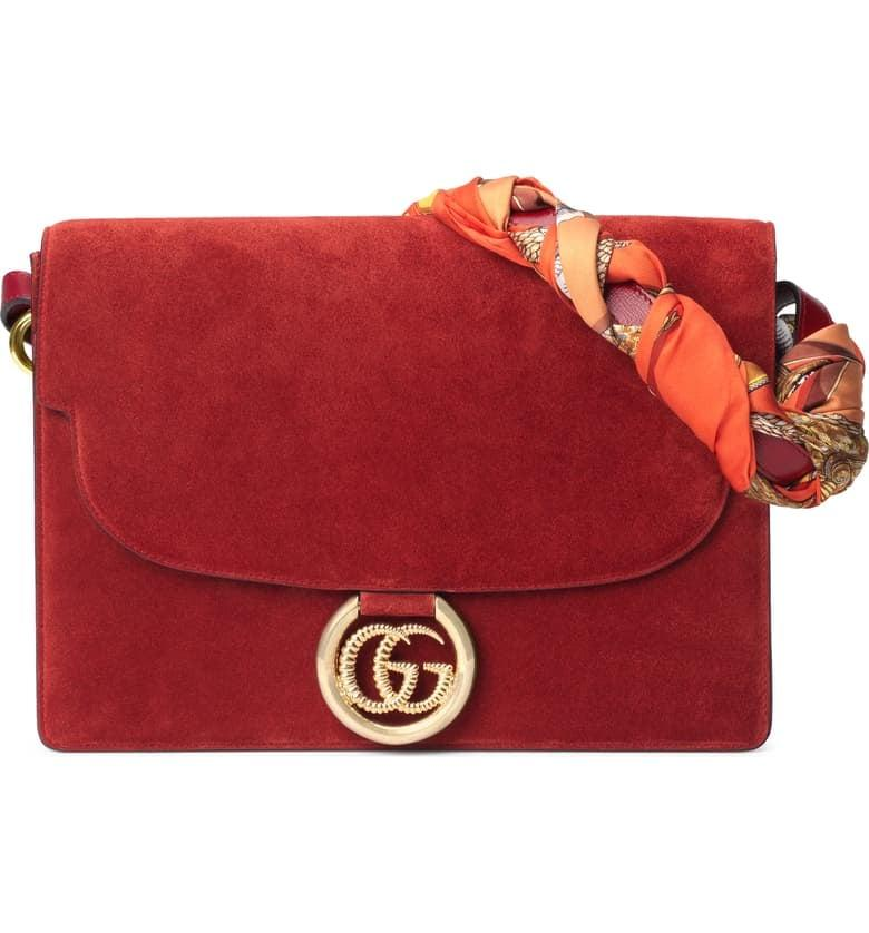 """<p>This timeless <a href=""""https://www.popsugar.com/buy/Gucci-Medium-GG-Ring-Suede-Shoulder-Bag-Horse-amp-Tassel-Foulard-Scarf-478885?p_name=Gucci%20Medium%20GG%20Ring%20Suede%20Shoulder%20Bag%20With%20Horse%20%26amp%3B%20Tassel%20Foulard%20Scarf&retailer=shop.nordstrom.com&pid=478885&price=3%2C200&evar1=fab%3Aus&evar9=46489553&evar98=https%3A%2F%2Fwww.popsugar.com%2Fphoto-gallery%2F46489553%2Fimage%2F46489916%2FGucci-Medium-GG-Ring-Suede-Shoulder-Bag-Horse-Tassel-Foulard-Scarf&list1=shopping%2Cfall%20fashion%2Caccessories%2Cbags%2Ctrends%2Cpurses%2Chandbags&prop13=api&pdata=1"""" rel=""""nofollow"""" data-shoppable-link=""""1"""" target=""""_blank"""" class=""""ga-track"""" data-ga-category=""""Related"""" data-ga-label=""""https://shop.nordstrom.com/s/gucci-medium-gg-ring-suede-shoulder-bag-with-horse-tassel-foulard-scarf/5364277?origin=category-personalizedsort&amp;breadcrumb=Home%2FWomen%2FHandbags&amp;color=new%20cherry%20red%2F%20orange"""" data-ga-action=""""In-Line Links"""">Gucci Medium GG Ring Suede Shoulder Bag With Horse &amp; Tassel Foulard Scarf</a> ($3,200) is an investment you'll enjoy for years.</p>"""