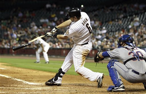 Houston Astros' Travis Buck (6) breaks his bat as he hits the ball as New York Mets catcher Josh Thole (30) reaches for the pitch during the sixth inning of a baseball game Monday, April 30, 2012, in Houston. (AP Photo/David J. Phillip)