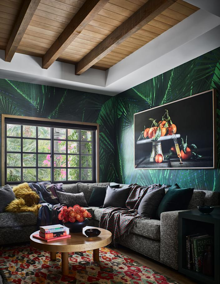 """In the media room, a custom green wallpaper from <a href=""""http://www.fliepaper.com"""" rel=""""nofollow noopener"""" target=""""_blank"""" data-ylk=""""slk:Flie Paper"""" class=""""link rapid-noclick-resp"""">Flie Paper</a> brings out the orange hues of the still-life photograph by <a href=""""https://www.curtisspeer.com"""" rel=""""nofollow noopener"""" target=""""_blank"""" data-ylk=""""slk:Curtis Speer"""" class=""""link rapid-noclick-resp"""">Curtis Speer</a>, which was commissioned specifically for the space. The sectional was custom made at Village Interiors and the round coffee table is from <a href=""""https://nickeykehoe.com"""" rel=""""nofollow noopener"""" target=""""_blank"""" data-ylk=""""slk:Nickey Kehoe"""" class=""""link rapid-noclick-resp"""">Nickey Kehoe</a>."""