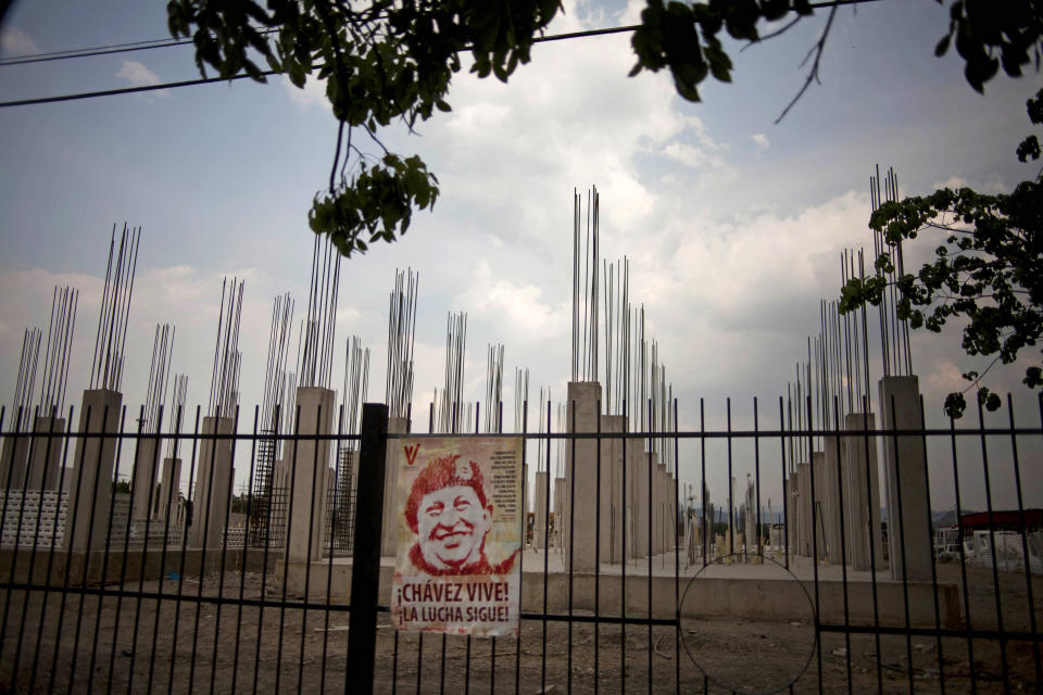 """In this April 8, 2013 photo, an image of Venezuela's late President Hugo Chavez is posted on an iron fence next to a government construction project of would be homes in Valencia, Venezuela. Outside Venezuela's capital, power outages, food shortages and unfinished projects abound; important factors heading into Sunday's election to replace socialist Chavez, who died last month after a long battle with cancer. An estimated 2 million of Venezuela's country's nearly 30 million people lack permanent homes, and one of Chavez's anti-poverty """"missions"""" builds them. But it's been slow going. The government says it has built 370,500 homes and apartments over the past two years, and more than 3 million people applied for them. (AP Photo/Ramon Espinosa)"""