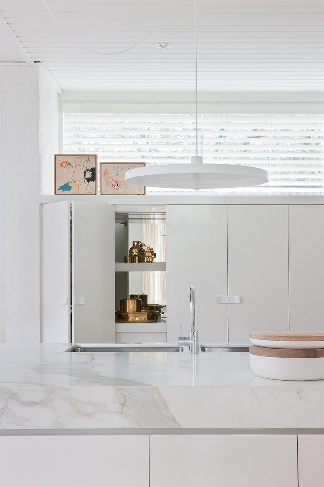 <p>Nothing in this kitchen designed by Hecker Guthrie was overlooked. Even the interiors of the cabinets are mirrored for a fun surprise. The mirrored cabinets, along with glossy white marble island and white disc pendant, creates the illusion of added sunlight and amplify the existing natural light pouring in. </p>