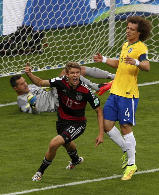 Germany's Thomas Mueller (C) celebrates past Brazil's David Luiz and goalkeeper Julio Cesar after scoring a goal during their 2014 World Cup semi-finals at the Mineirao stadium in Belo Horizonte July 8, 2014. REUTERS/David Gray (BRAZIL - Tags: SOCCER SPORT WORLD CUP)