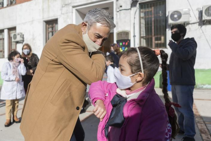 "<div class=""inline-image__caption""> <p>A school official greets a student during the first day of the final phase of reopening schools in Montevideo, Uruguay. </p> </div> <div class=""inline-image__credit""> Ernesto Ryan/Getty </div>"