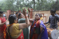 Hindu women dance in the rain to celebrate ahead of a groundbreaking ceremony of a temple dedicated to the Hindu god Ram in Ayodhya, at the Vishwa Hindu Parishad, or World Hindu Council, headquarters in New Delhi, India, Wednesday, Aug. 5, 2020. The coronavirus is restricting a large crowd, but Hindus were joyful before Prime Minister Narendra Modi breaks ground Wednesday on a long-awaited temple of their most revered god Ram at the site of a demolished 16th century mosque in northern India. (AP Photo/Manish Swarup)
