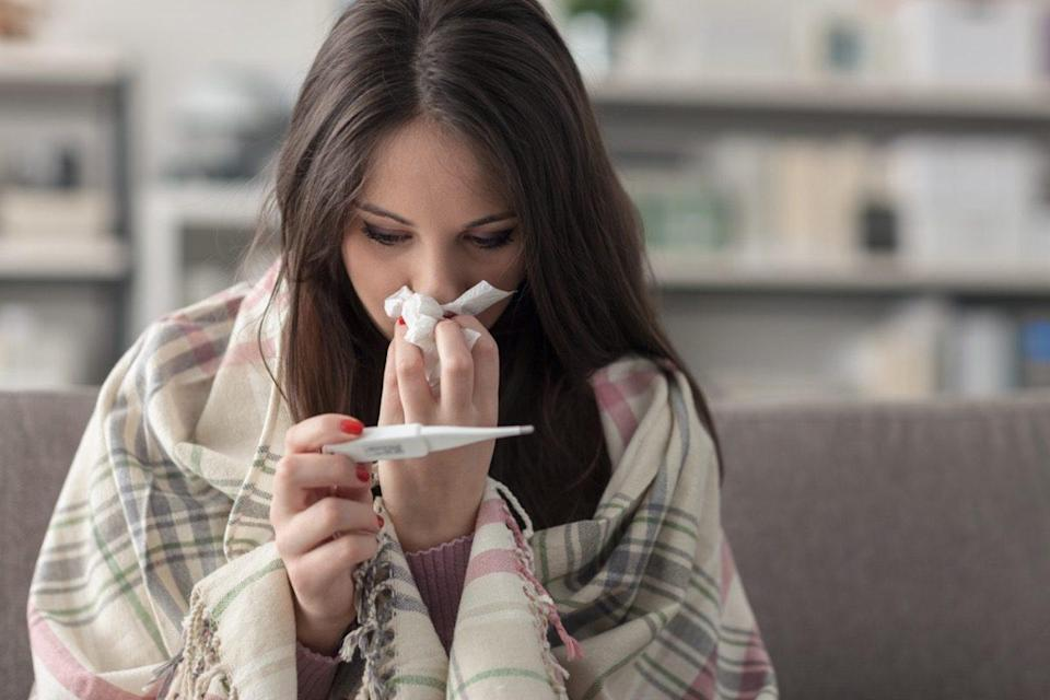 Sick young woman at home on the sofa, she is covering with a blanket, taking temperature and blowing her nose with a tissue