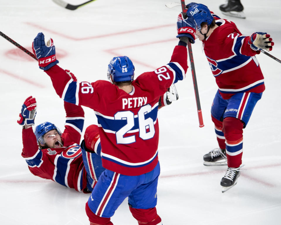 Montreal Canadiens' Josh Anderson (17) slides on the ice as he celebrates his winning goal alongside teammates Jeff Petry (26) and Alexander Romanov (27) during overtime of Game 4 of the NHL hockey Stanley Cup final against the Tampa Bay Lightning in Montreal, Monday, July 5, 2021. (Ryan Remiorz/The Canadian Press via AP)