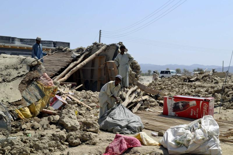 Survivors collect their belongings near the rubble of a mud house after it collapsed following an earthquake in the town of Awaran