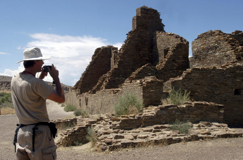 FILE - In this Aug. 10, 2005 file photo, tourist Chris Farthing from Suffolks County, England, takes a picture of Anasazi ruins in Chaco Culture National Historical Park in New Mexico. The checkerboard of federal land surrounding Chaco Culture National Historical Park would be off limits to oil and gas development under legislation pending before Congress. The U.S. House is set to vote on the measure Wednesday, Oct. 30, 2019. (AP Photo/Jeff Geissler, File)