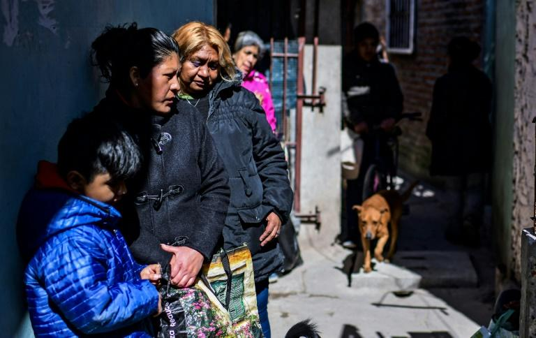 People wait for food outside Avia's house, where a soup kitchen feeds at least 200 people a day