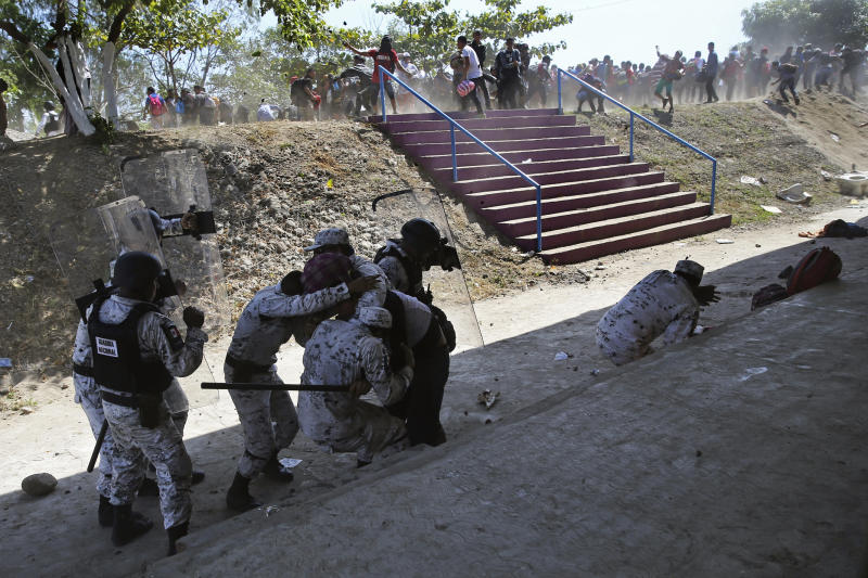 Mexican National Guards detain a Central American migrant, partially covered, as some migrants throw rocks at them after the group crossed from Guatemala to Mexico, near the bank of the Suchiate River near Ciudad Hidalgo, Mexico, Monday, Jan. 20, 2020. More than a thousand Central American migrants hoping to reach the United States marooned in Guatemala are walking en masse across a river leading to Mexico in an attempt to convince authorities there to allow them passage through the country. (AP Photo/Marco Ugarte)