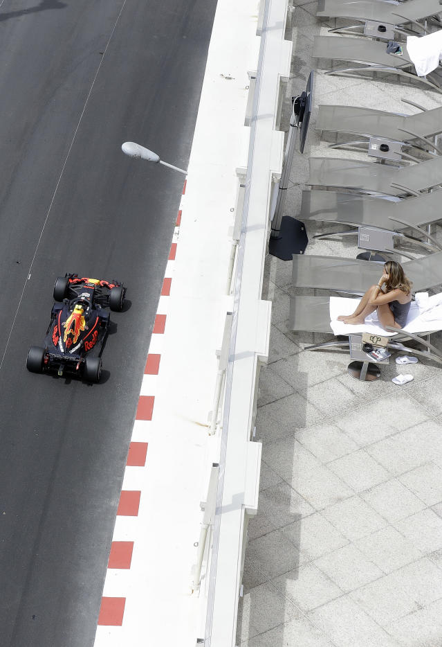 A woman watches Red Bull driver Max Verstappen of the Netherlands steering his car during a practice session in Monaco, Thursday, May 24, 2018. The Formula one race will be held on Sunday. (AP Photo/Luca Bruno)