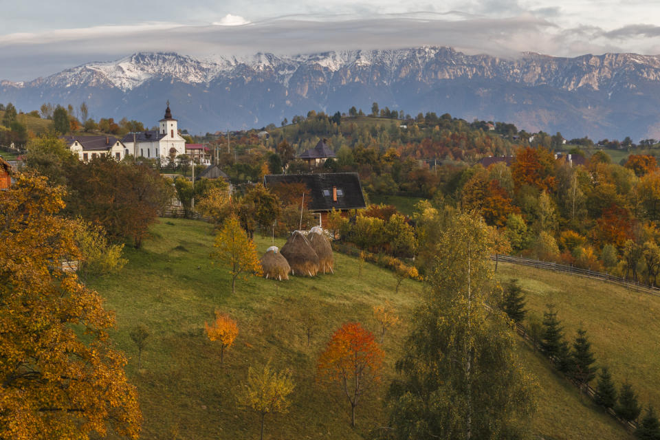 Autumn alpine landscape, with spectacular gardens and high snowy mountains in background near Bran, Magura, Transylvania, Romania. (PHOTO: Getty Images)