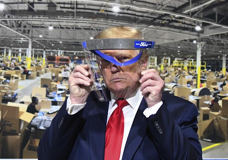 President Donald Trump looks through a face shield, in front of poster of the manufacturing of these shields, while touring Ford Motor Co.'s Rawsonville Components Plant in Ypsilanti, Michigan on Thursday, May 21, 2020.