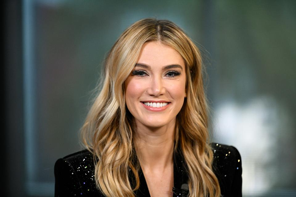 """Delta Goodrem wears a black jacket and her wavy blonde hair loose for an appearance on """"Extra"""" at Universal Studios Hollywood on January 31, 2019 in Universal City, California."""